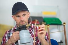 Tradesman using a blowtorch. Man Stock Photography