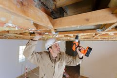 Tradesman using drill on wooden framework for ceiling. Drill stock image