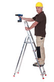 Tradesman using a power tool. While standing on a stepladder Royalty Free Stock Photos