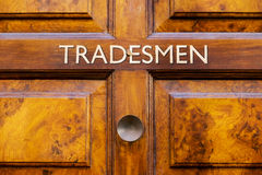 Tradesmens entrance door. A vintage wooden door with tradesmen sign Royalty Free Stock Photos