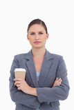 Tradeswoman with arms folded and paper cup Stock Photography