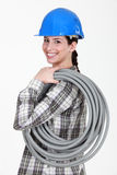 Tradeswoman carrying corrugated tubing Stock Images