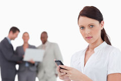 Tradeswoman with cellphone and associates behind her Royalty Free Stock Photo