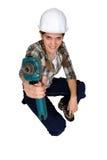 Tradeswoman che per mezzo di un attrezzo a motore Immagini Stock