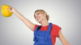 Tradeswoman dancing with a pencil on gradient background. royalty free stock photography