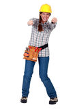 Tradeswoman gripping an invisible object. And squinting Stock Photo