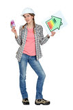 Tradeswoman holding energy efficiency chart. Tradeswoman holding up an energy efficiency rating chart and a wad of money royalty free stock images