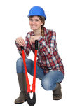 Tradeswoman holding pliers. A tradeswoman holding oversized pliers Royalty Free Stock Images