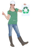 Tradeswoman holding the recycling symbol. And giving the thumb's up Stock Photography