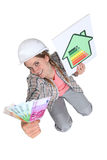Tradeswoman holding up a wad of cash royalty free stock images
