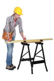 Tradeswoman measuring a plank Royalty Free Stock Photography
