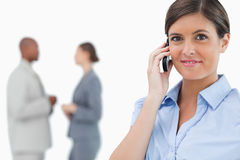 Tradeswoman with mobile phone and associates behind her Stock Photo