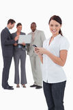 Tradeswoman with mobile phone and colleagues behind her Stock Images
