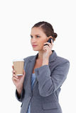 Tradeswoman with paper cup on her cellphone Royalty Free Stock Photography