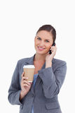 Tradeswoman with paper cup on her cellphone Royalty Free Stock Photos