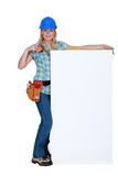 Tradeswoman by a sign Royalty Free Stock Photos