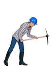 Tradeswoman using a pickaxe. Tradeswoman using a sharp pickaxe Stock Photo