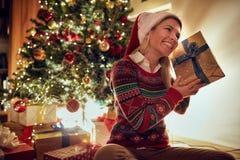 Tradição do Natal - a mulher no chapéu de Santa com Natal presen imagens de stock