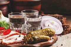 Tradição do russo: vodca fria e um petisco do bacon, salmouras, vermelhas imagem de stock