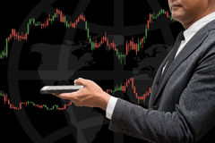 Trading Businessman hold smart phone.and Forex Trading Line Grap. Trading Businessman hold smart phone.and Forex Trading Lines Graphs Stock Photography