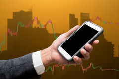 Trading Businessman hold smart phone.and Forex Trading Line Grap. Trading Businessman hold smart phone.and Forex Trading Lines Graphs Royalty Free Stock Photos