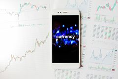 Trading on the currency exchange, concept. Reports and statistics, volatility of currency. Smartphone with an inscription on the screen stock photos