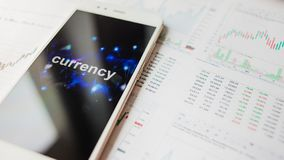Trading on the currency exchange, concept. Reports and statistics, volatility of currency. Smartphone with an inscription on the screen royalty free stock photos