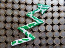 Arrow up formed with plasticine in green and white and stacked coins of mexican pesos. Trading and exchange, bank and commerce, price of buy and sell, cash value royalty free stock photos