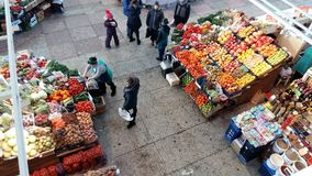 Trading range with fruits, sellers and buyers royalty free stock photos