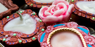 Tradional indian diya and wax rose. Tradional earthenware lamps (diya) hand made and decorated. Wax rose candle in the center Royalty Free Stock Photo