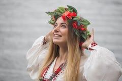 Tradisionalslut och krans för ung lycklig kvinna bärande arkivfoto
