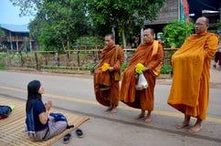 Tradition av almsgiving med klibbiga ris av munkprocessionen Arkivfoto