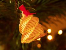 Tradition Christmas bell decoration made from dry straw. Christmas tree with small gentle lights. Stock Photos