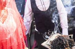 Tradition de Shamanic pour la bonne chance en Turquie rurale L'encens des bâtons d'herbe fume va à de jeunes couples dans une cér image libre de droits
