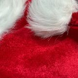 Red Santa Claus hat with fluffy white ball stock photo