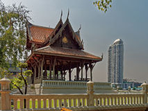 Tradition and Modernity in Bangkok. A traditional Thai pavilion with a modern skyscraper in the background as a symbol of the contrast between tradition and Royalty Free Stock Images