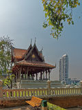 Tradition and Modernity in Bangkok. A traditional Thai pavilion with a modern skyscraper in the background as a symbol of the contrast between tradition and Stock Images
