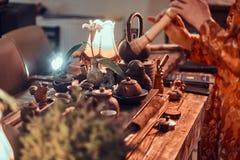 Tradition, santé, harmonie Cérémonie de thé chinoise Le maître de thé dans le kimono exécute dans la chambre noire avec un intéri photos stock
