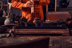 Tradition, sant?, harmonie C?r?monie de th? chinoise Le ma?tre de th? dans le kimono ex?cute dans la chambre noire avec un int?ri images libres de droits