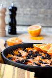 Tradition Seafood Spanish Paella in authentic iron pan. Tradition Spanish dish - valencian seafood Paella in authentic pan paellera with black pepper mill and Stock Photos