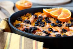 Tradition Seafood Spanish Paella in authentic iron pan. Tradition Spanish dish - valencian seafood Paella in authentic pan paellera with sackcloth and red orange Royalty Free Stock Photo