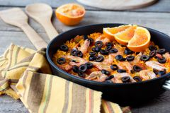 Tradition Seafood Spanish Paella in authentic iron pan. Tradition Spanish dish - valencian seafood Paella in authentic pan paellera with sackcloth and red orange stock photography