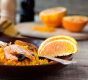 Tradition Seafood Spanish Paella in ceramic dish. Tradition Spanish dish - valencian seafood Paella in ceramic dish with black and white Pepper and Salt Mill in Royalty Free Stock Photography