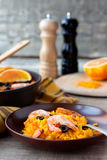 Tradition Seafood Spanish Paella in ceramic dish. Tradition Spanish dish - valencian seafood Paella in ceramic dish with black and white Pepper and Salt Mill in Stock Photos