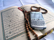 Tradition and Technology. Quran with prayer beads with a Smartphone royalty free stock images