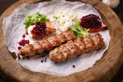 Traditional Adana kebab on wooden plate. With marinated onion garnishing and spicy aromatic herbs. Delicious meat, Turkish cuisine stock image