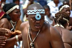 Traditional African dancers. African dancers in traditional dress with male in foreground stock photography