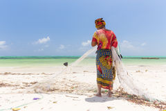 Traditional african local rural fishing on Paje beach, Zanzibar, Tanzania. Traditionally dressed local woman pulling fishing net, catching small fish Royalty Free Stock Images