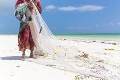 Traditional african local rural fishing on Paje beach, Zanzibar, Tanzania. Traditionally dressed local woman pulling fishing net, catching small fish Royalty Free Stock Image
