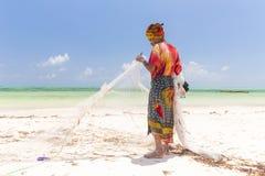 Traditional african local rural fishing on Paje beach, Zanzibar, Tanzania. Traditionally dressed local woman pulling fishing net, catching small fish Stock Photo